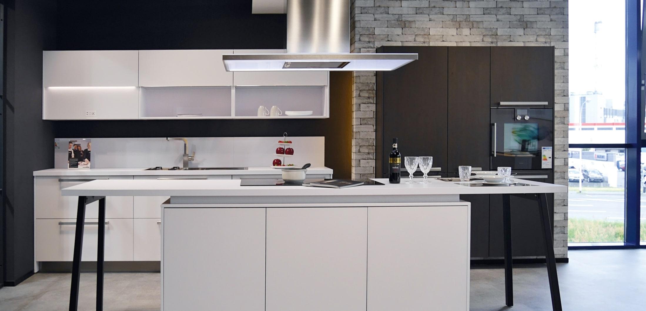 weiße Küche mit moderner Dunstabzugshaube und Kücheninsel