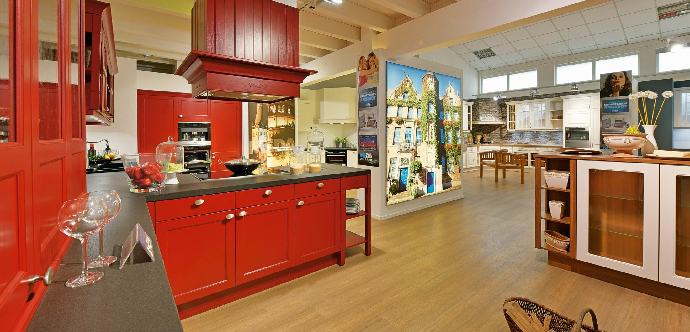 Küche mit roter Front und modernen Küchengeräten.