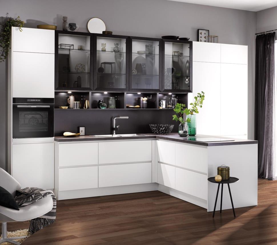Weiße Küche mit dunklen Hängenschränken und Glastür